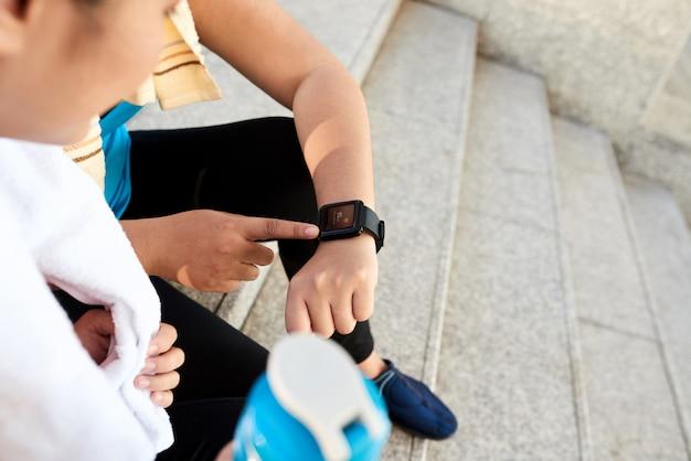 Corredores femininos urbanos irreconhecíveis, olhando para o relógio inteligente na rua