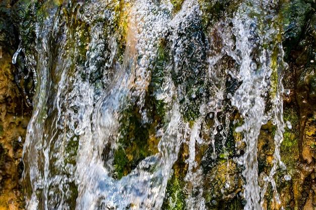 Córrego da montanha que flui rapidamente, close-up de água fluindo da rocha.