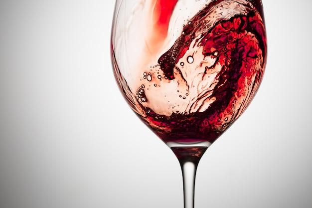Córrego do vinho que está derramando em um vidro.