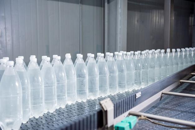 Correia transportadora com garrafas de água potável em uma moderna fábrica de bebidas