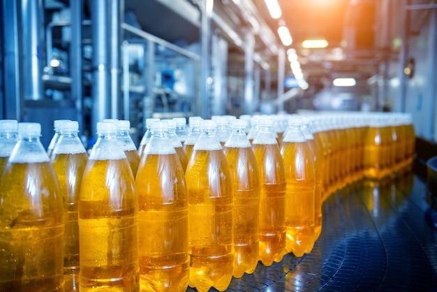 Correia transportadora com garrafas para suco ou água em uma moderna fábrica de bebidas
