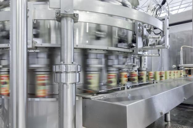 Correia transportadora em movimento na produção e engarrafamento de bebidas em latas