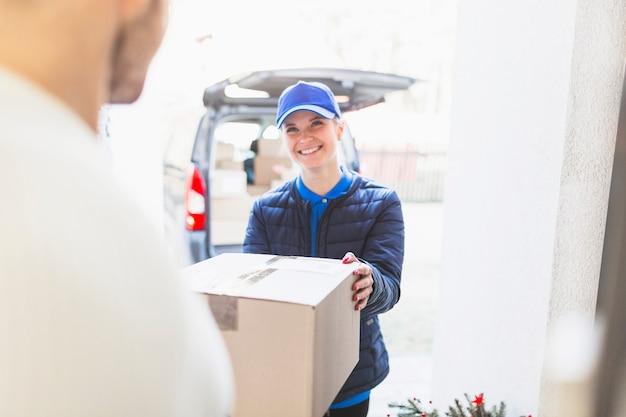 Correio alegre que dá pacote ao cliente
