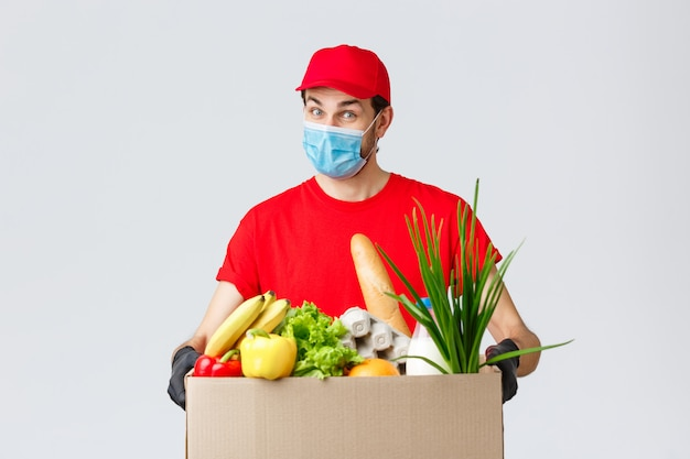 Correio amigável com máscara facial e luvas, uniforme vermelho traz caixa de alimentos para o cliente solicitado on-line, entrega sem contato