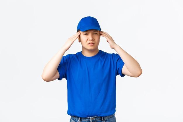 Correio asiático com problemas de boné azul e camiseta parecendo tonto ou sobrecarregado. o entregador não consegue lidar com a pressão, tocando a cabeça, sentindo dor de cabeça ou cansaço, fundo branco de pé