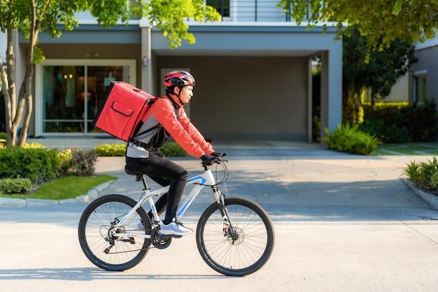Correio asiático do homem na bicicleta que entrega o alimento nas ruas da cidade com uma entrega quente do alimento de takeways e restaurantes à casa, entrega expressa da comida e conceito em linha da compra.