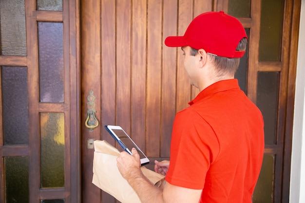 Correio caucasiano em frente à porta e segurando o tablet. carteiro profissional entregando pedidos em casa e esperando o cliente. serviço de entrega expressa e conceito de compra online