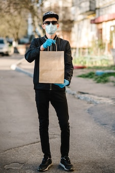 Correio com máscara protetora, luvas médicas fornece comida para viagem. empregado segurar pacote de papelão. lugar para texto. serviço de entrega em quarentena, 2019-ncov, coronavírus pandêmico, covid-19.