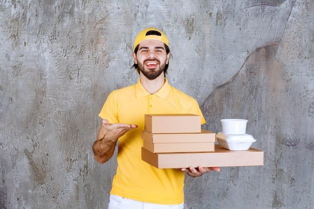 Correio com uniforme amarelo segurando pacotes para viagem e caixas de papelão