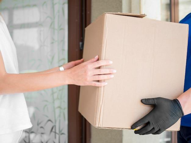 Correio de close-up que entrega o pacote