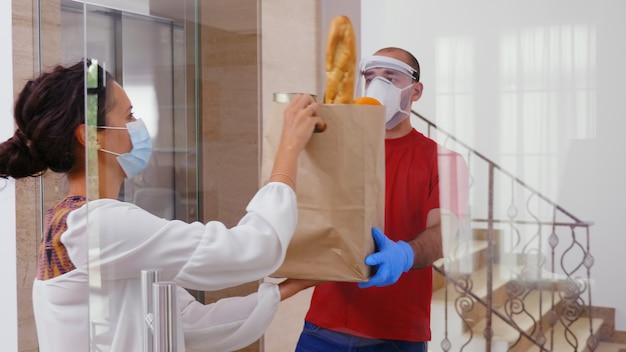Correio de comida com máscara de proteção entregando mantimentos para uma mulher durante covid-19.