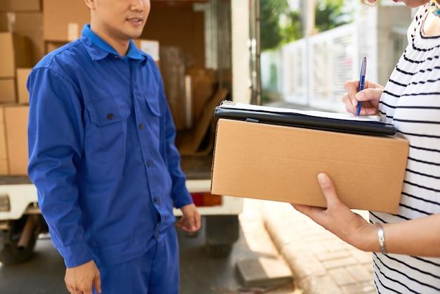 Correio de empresa de mudança de casa em uniforme azul olhando para mulher assinando documentos de serviço de entrega