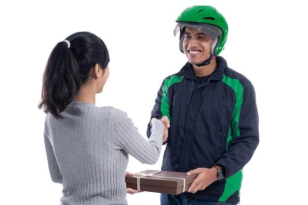 Correio de entrega com capacete e uniforme enviando pacote para cliente