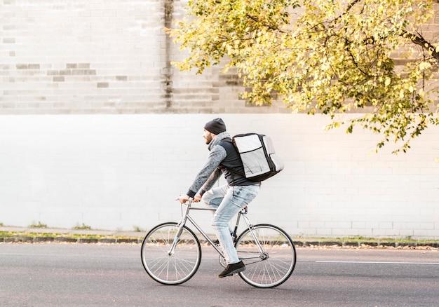 Correio de entrega de comida andando de bicicleta a caminho de entregar um pedido o mais rápido possível