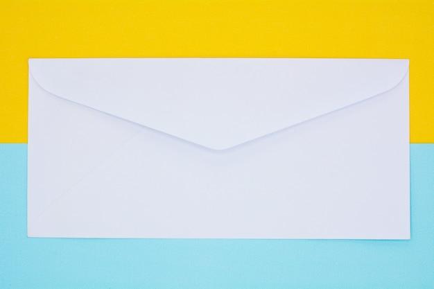 Correio de envelope branco sobre fundo amarelo e azul