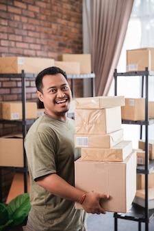 Correio de homem segurando o trabalho de pacote no negócio de pacotes de transporte
