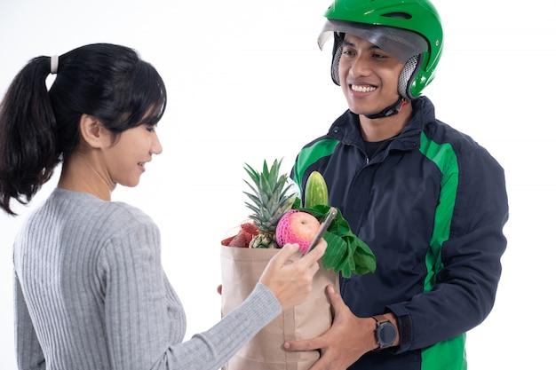 Correio de motorista com comida enviando pedido on-line para o cliente
