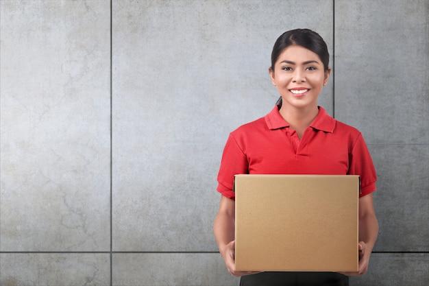 Correio de mulher muito asiática com caixa de papelão