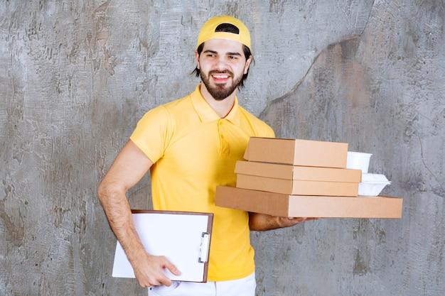 Correio de uniforme amarelo segurando pacotes para viagem e sacola de compras e pedindo uma assinatura