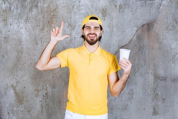 Correio de uniforme amarelo segurando um copo descartável e pensando ou tendo uma boa ideia.