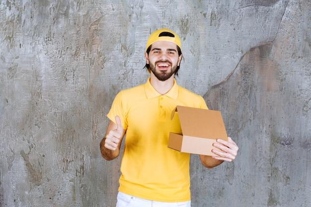 Correio de uniforme amarelo segurando uma caixa de papelão aberta e apreciando o produto