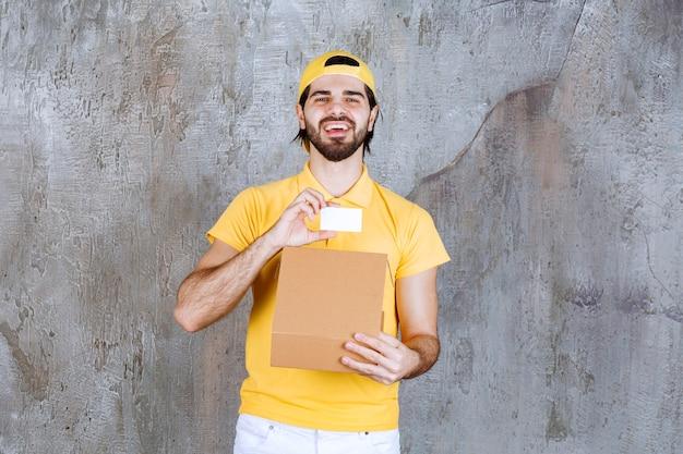 Correio de uniforme amarelo segurando uma caixa de papelão aberta e apresentando um cartão de visita