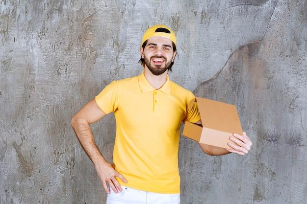 Correio de uniforme amarelo segurando uma caixa de papelão aberta