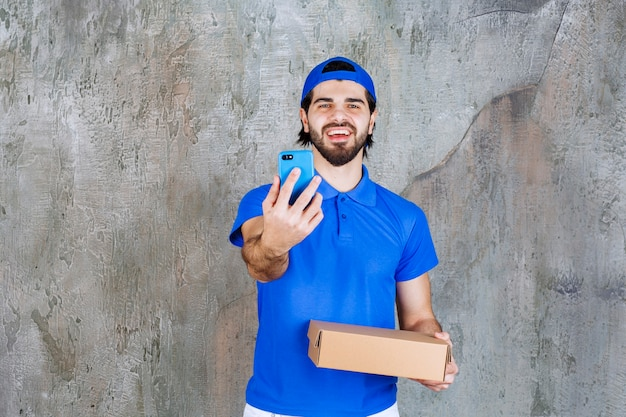 Correio de uniforme azul segurando uma caixa para viagem e fazendo uma videochamada.