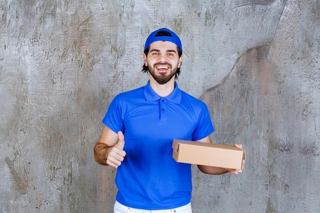 Correio de uniforme azul segurando uma caixa para viagem e mostrando um sinal positivo com a mão.