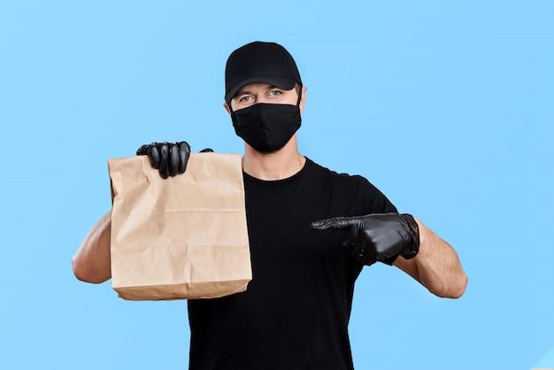 Correio de uniforme preto, segurando um saco de papel