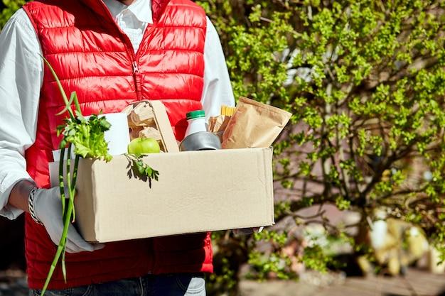 Correio em máscara protetora e luvas médicas entrega caixa de alimentos. entrega em domicílio de alimentos durante surtos de vírus, pânico por coronavírus e pandemias. fique seguro. homem mantém caixa de doação com comida.