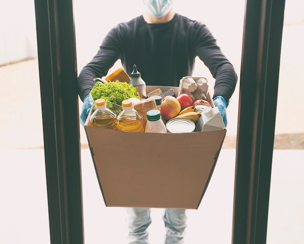 Correio entregando caixa ecológica de papelão com mantimentos