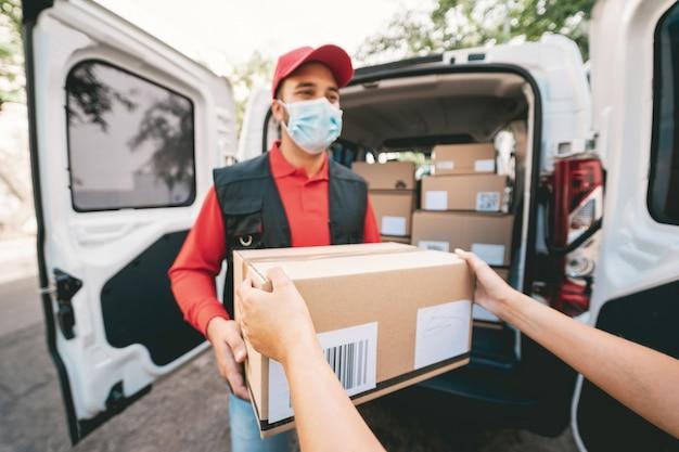 Correio entregando pacotes com caminhão usando máscara protetora