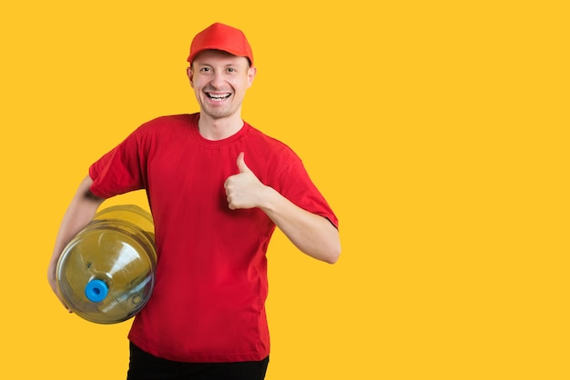 Correio feliz em uniforme vermelho amarelo com garrafa de água aparecendo com os polegares para cima