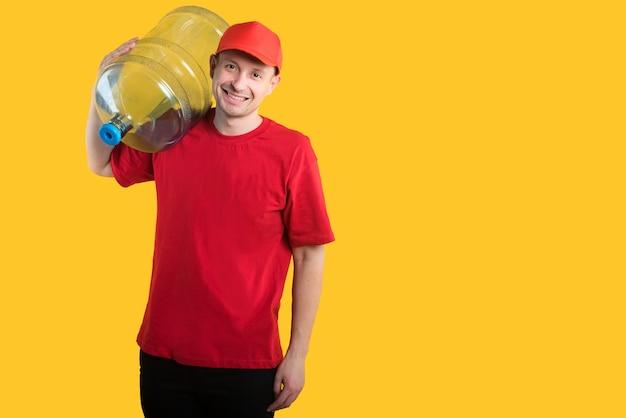 Correio feliz em uniforme vermelho amarelo com garrafa de água