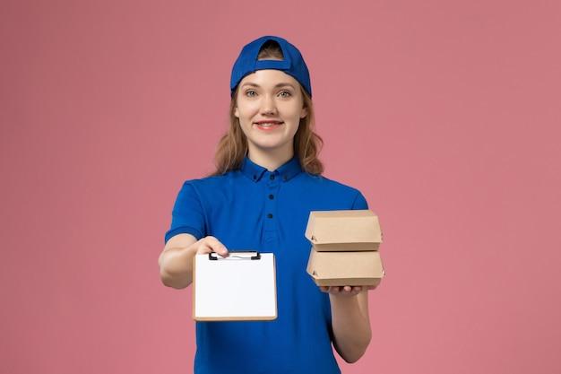 Correio feminino com capa de uniforme azul, vista frontal, segurando pequenos pacotes de comida de entrega e um bloco de notas no trabalho de funcionário de serviço de entrega de fundo rosa