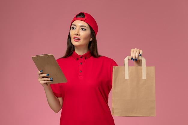 Correio feminino com capa de uniforme vermelha, vista frontal, pacote de entrega de papel e bloco de notas nas mãos na parede rosa, entregador de uniforme