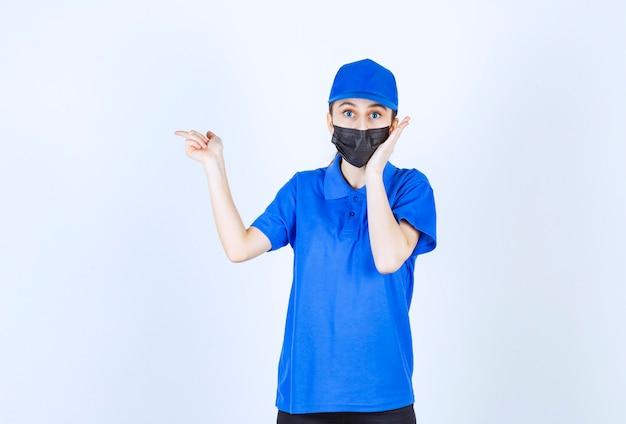 Correio feminino com máscara e uniforme azul apontando para o lado esquerdo.