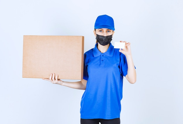 Correio feminino com máscara e uniforme azul, segurando um grande pacote de papelão e apresentando seu cartão de visita.