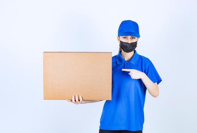 Correio feminino com máscara e uniforme azul, segurando um grande pacote de papelão.