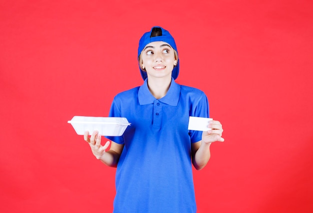 Correio feminino com uniforme azul, segurando uma caixa de take-away branca e um cartão de visita e parece pensativo.