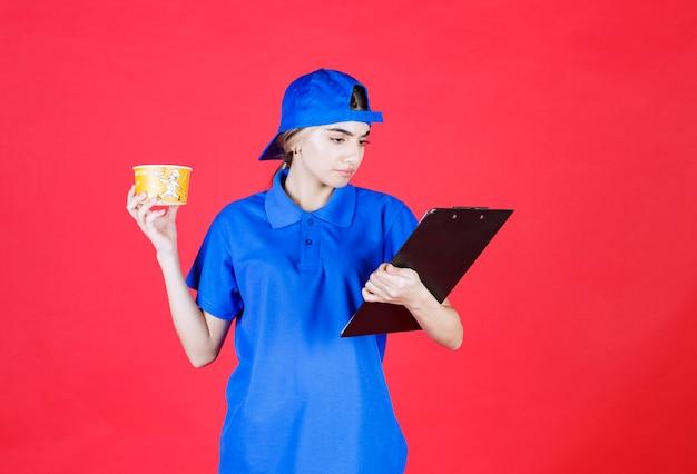 Correio feminino com uniforme azul, segurando uma xícara de macarrão amarelo e verificando o endereço na lista de clientes.