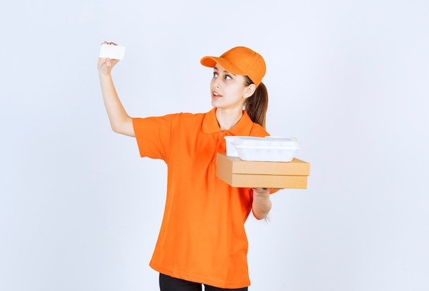 Correio feminino com uniforme laranja segurando uma caixa de papelão e uma caixa de plástico para viagem enquanto apresenta seu cartão de visita.