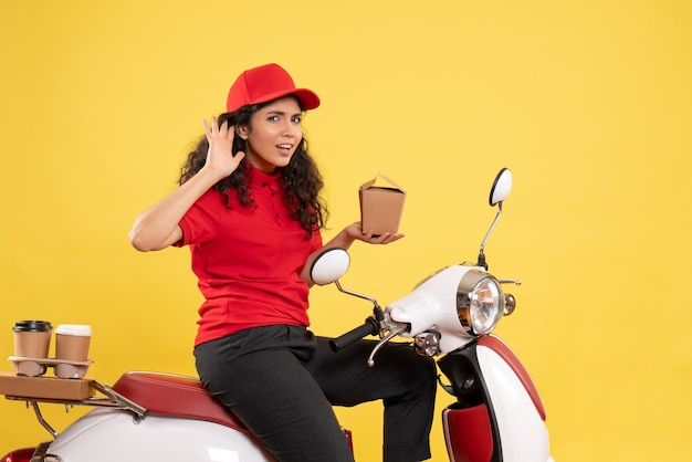 Correio feminino de frente para a bicicleta para entrega de café e comida em um fundo amarelo serviço trabalho entrega uniforme trabalhador trabalho mulher