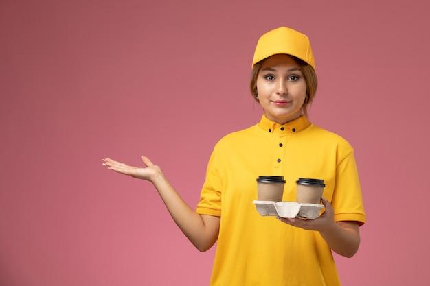 Correio feminino de frente para a capa uniforme amarela segurando copos de café de plástico no fundo rosa. trabalho de entrega uniforme