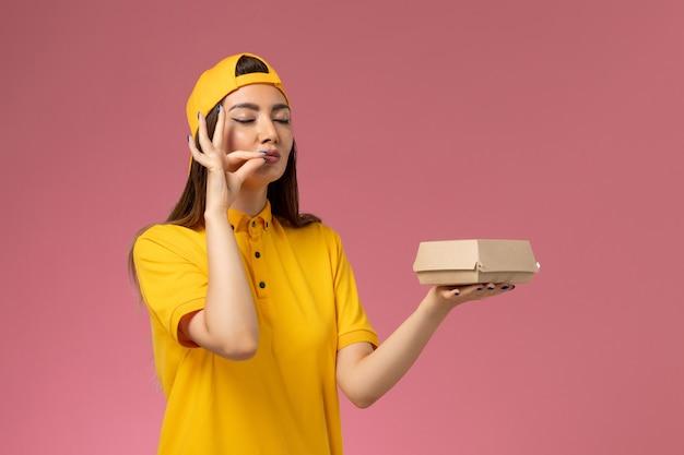 Correio feminino de frente para o uniforme amarelo e capa segurando um pequeno pacote de entrega de comida na parede rosa.
