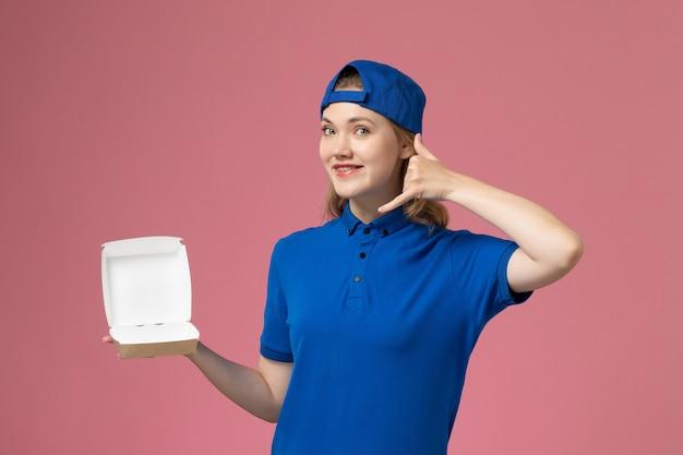 Correio feminino de frente para o uniforme azul e capa segurando um pequeno pacote de entrega de comida no fundo rosa.