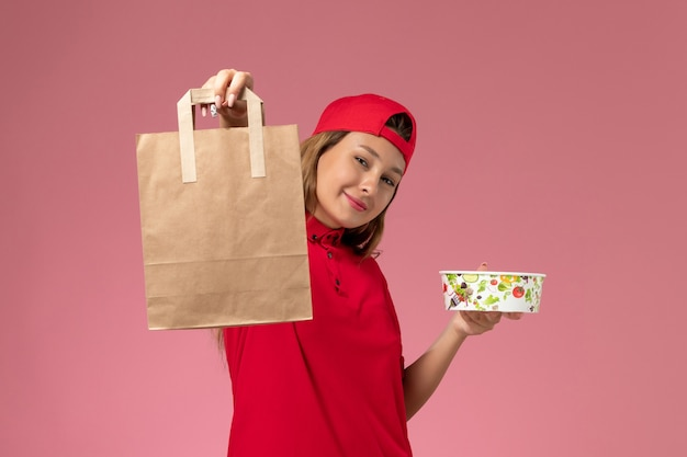 Correio feminino de frente para o uniforme vermelho e capa segurando o pacote de comida de entrega e a tigela na parede rosa, trabalhador de serviço de trabalho de entrega uniforme