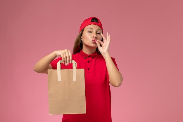 Correio feminino de frente para o uniforme vermelho e capa segurando o pacote de comida de entrega no fundo rosa.