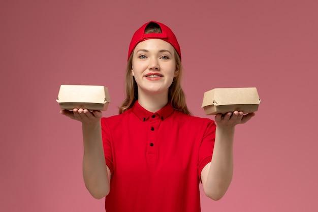 Correio feminino de frente para o uniforme vermelho e capa segurando pequenos pacotes de comida de entrega na parede rosa, trabalho de uniforme de empresa de serviço de entrega de trabalho